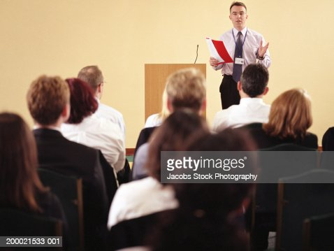 Businessman beside podium addressing colleagues : Stock Photo
