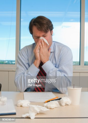Businessman blowing his nose : Stock Photo
