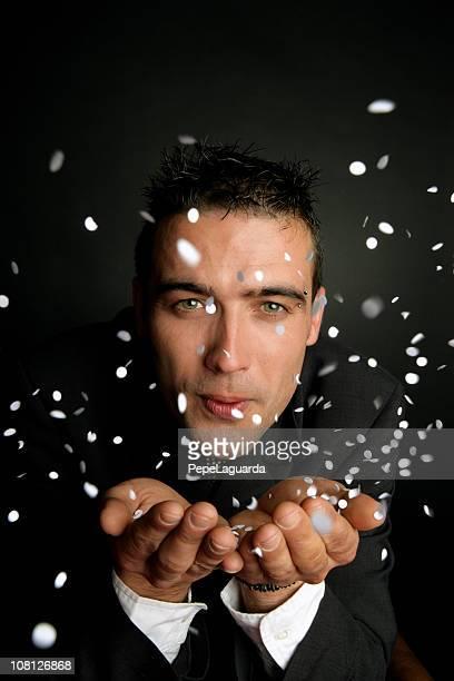 Geschäftsmann Blasen weißes Konfetti auf schwarzem Hintergrund