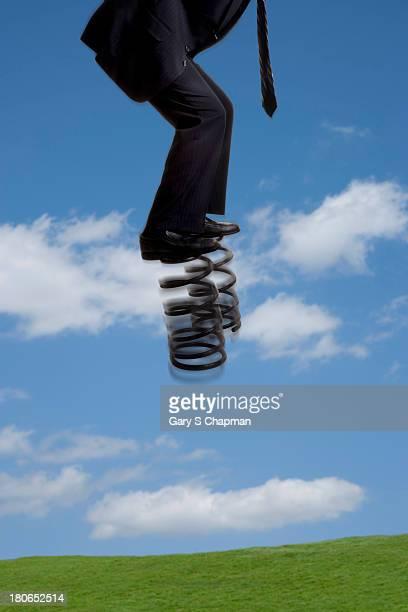 Businessman bouncing on large springs