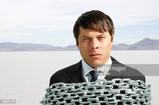 Businessman Bound in Chains in Desert.