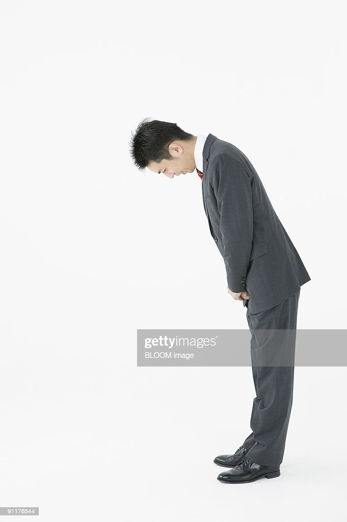 Businessman bowing, side view, studio shot