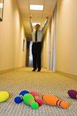 Businessman bowling in hallway