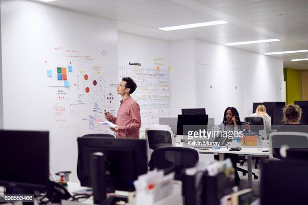 Businessman brainstorming in open plan creative office