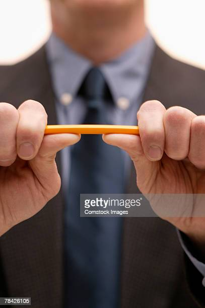 Businessman breaking a pencil