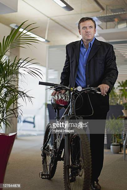Businessman bringing bicycle into office