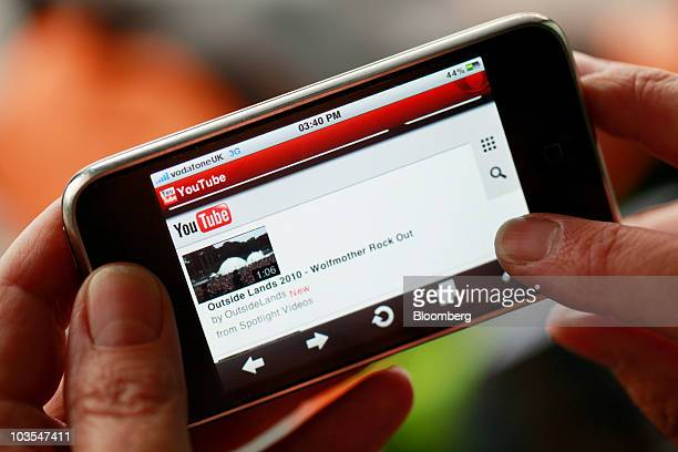 A businessman browses Google Inc�s YouTube website using an Apple iPhone made by Apple Inc in this arranged photograph in London UK on Thursday Aug19...