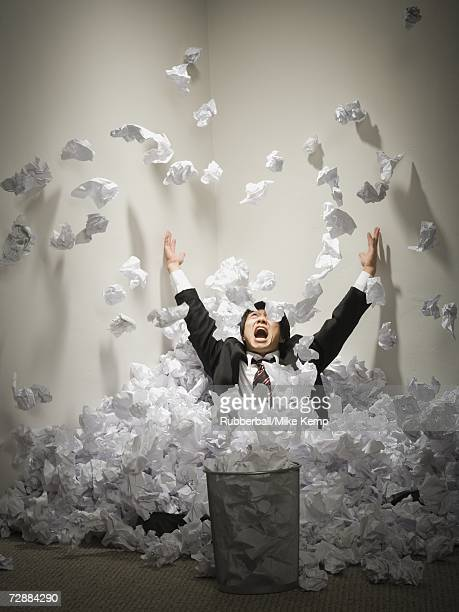Businessman buried in mountain of crumpled papers