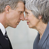 Businessman & Businesswoman Face To Face In Street