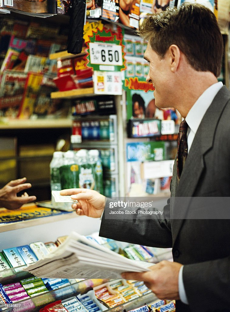 Businessman buying newspaper at convenience store
