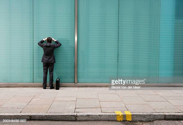 Businessman by building, looking into window, rear view