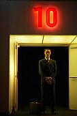 Businessman by door under neon '10' sign, portrait