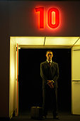 Businessman by door under neon '10' sign, portrait