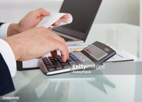 Businessman Calculating Expense In Office : Stock Photo