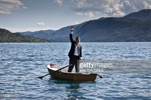 Businessman calling for help in rowboat