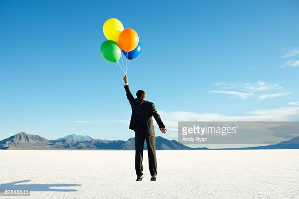 Businessman carried away by balloons