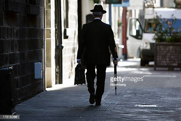 A businessman carries a briefcase and umbrella as he walks along a street in Edinburgh UK on Wednesday July 31 2013 The latest opinion polls show...