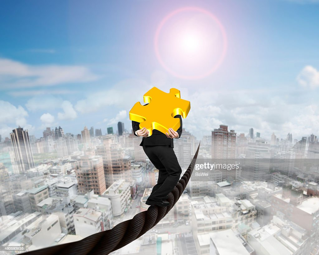 Businessman carrying 3D gold puzzle piece balancing on wire : Stock Photo