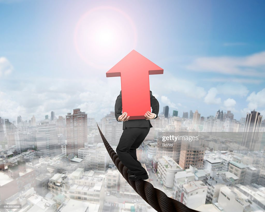 Businessman carrying 3D red arrow sign balancing on wire : Stock Photo