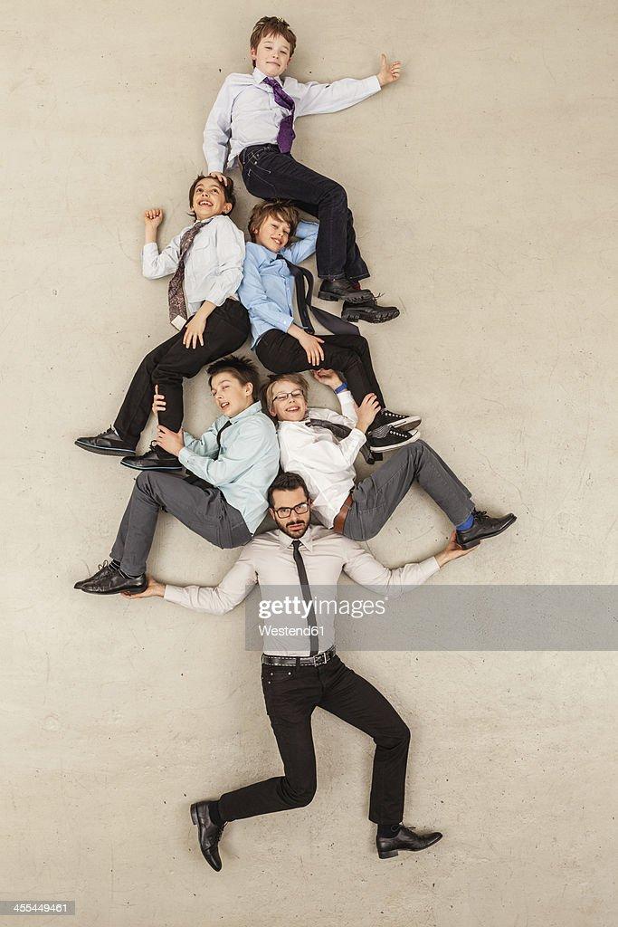 Businessman carrying boys on shoulder