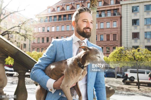 Businessman carrying dog while standing on steps