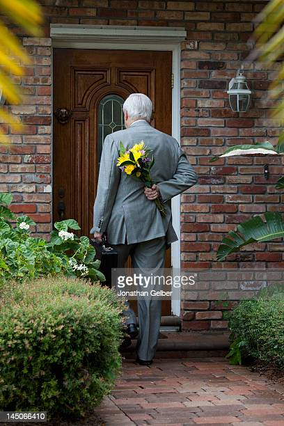 A businessman carrying flowers behind his back, arriving home