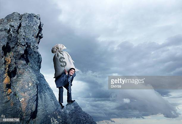 Businessman Carrying Large Money Bag Up A Hill