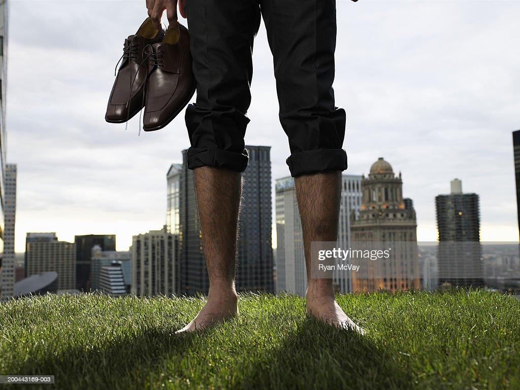 Businessman carrying shoes in grass field (low section)