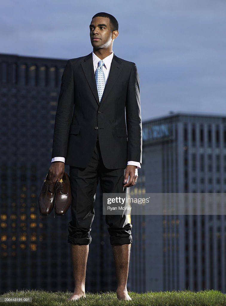 Businessman carrying shoes in grass field