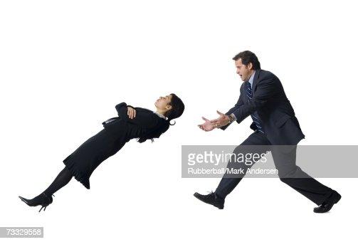 Businessman catching falling businesswoman