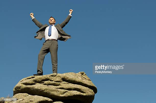 Businessman Celebrates Victory on Rocky Mountaintop