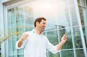 Businessman celebrating his success on smartphone