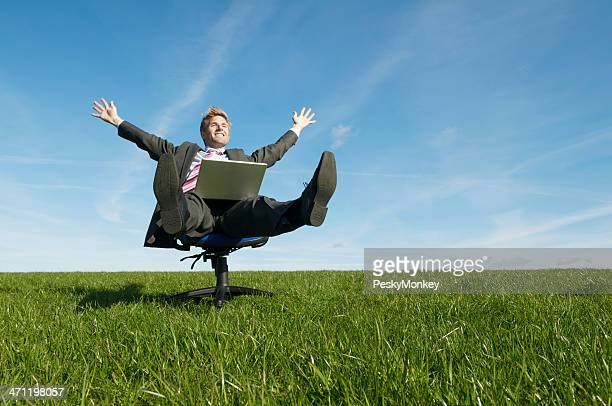 Businessman Celebrating Success in a Chair on the Meadow
