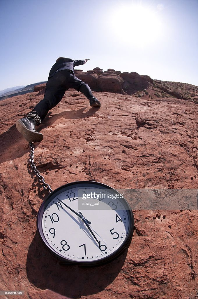 Businessman chained to the clock : Stock Photo