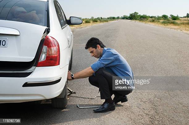 Businessman changing the punctured tire of his car