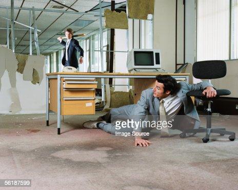 Businessman chasing colleague with a baseball bat