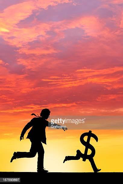 Businessman chasing money dollar sign