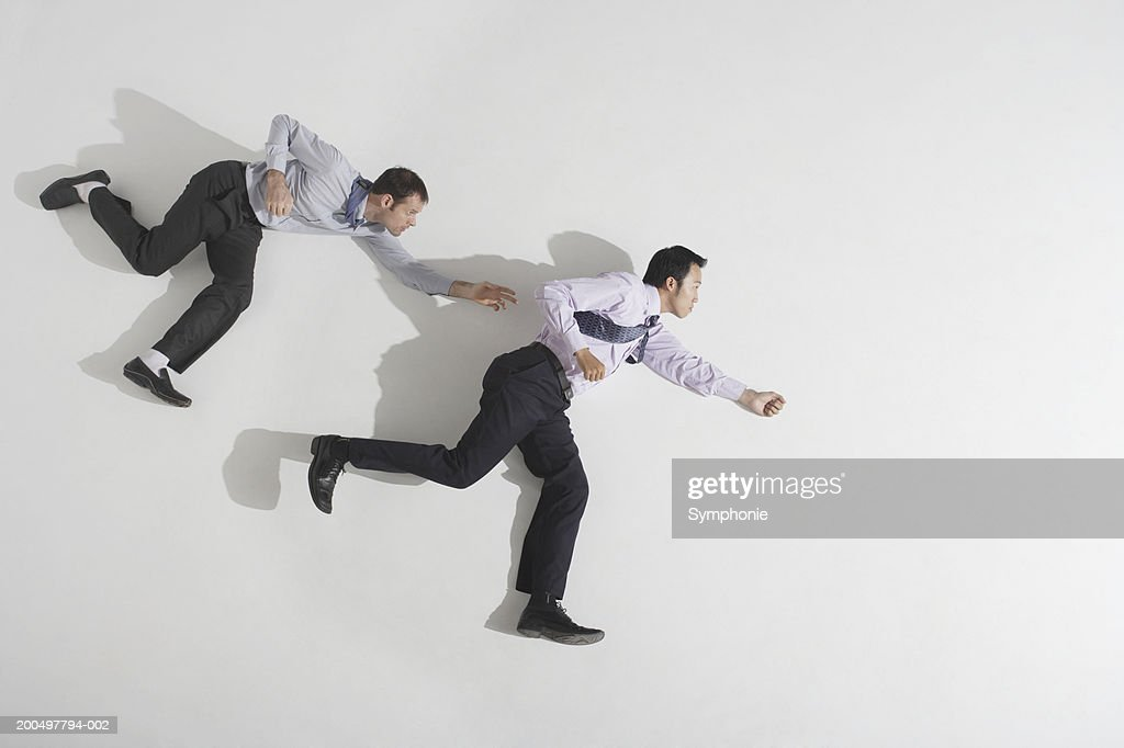 Businessman chasing second businessman, overhead view : Stock Photo