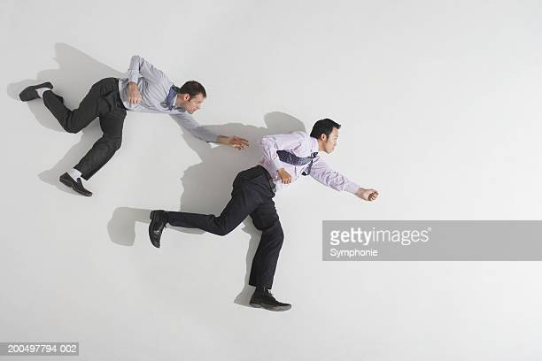 Businessman chasing second businessman, overhead view