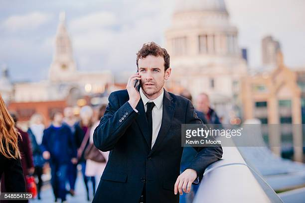 Businessman chatting on smartphone whilst leaning on millennium bridge, London, UK