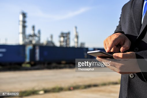 Businessman checking around oil refinery plant with clear sky : Stock Photo