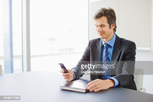 Businessman checking cell phone in conference room : Stock Photo