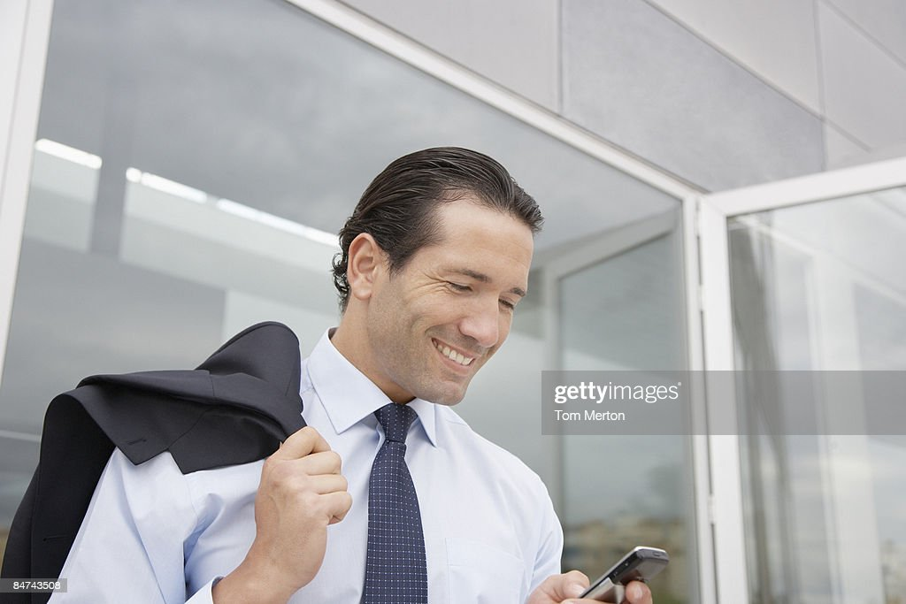 Businessman checking cell phone outdoors : Stock Photo