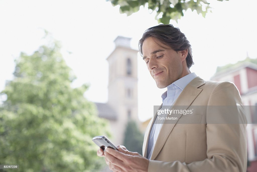 Businessman checking electronic organizer outdoors : Stock Photo