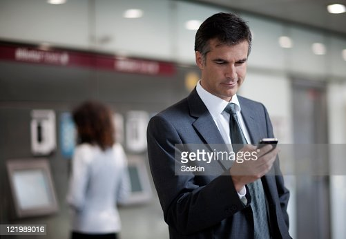 businessman checking emails in trainstation : Stock Photo