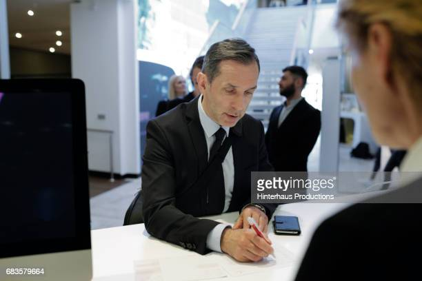 Businessman Checking Into A Hotel At Reception