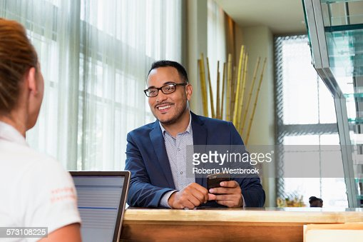 Businessman checking into hotel with concierge