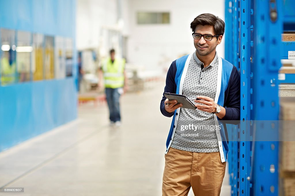 Businessman checking inventory in stock room : Stock Photo