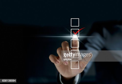 businessman checking mark on checklist with a red marker : Stock Photo