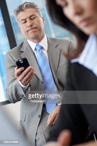 Businessman checking mobile phone near colleague